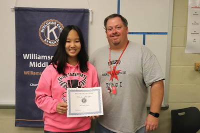 Builders Club advisor and seventh-grade math teacher Mike Lundy presents rising eighth-grader and incoming club treasurer Marcella Fisher with a certificate for completing 78.5 volunteer hours this school year.