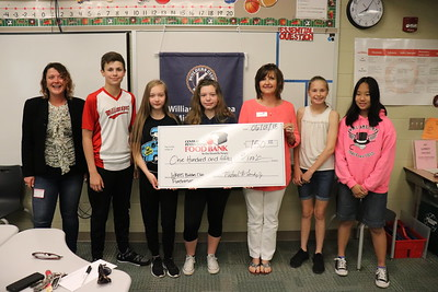 Central Pennsylvania Food Bank representatives Cydne Shull, left, and Pam Hicks, third from right, accept a $150 donation.  From left are Builders Club members Caleb Fausnaught, Mychal Flanigan, Savannah Grove, Sarah Spring and Marcella Fisher.