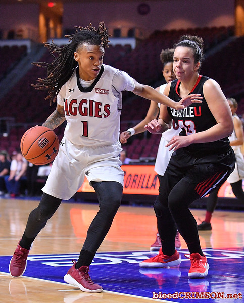 LAS VEGAS, NV - MARCH 09:  Jasmine Cooper #1 of the New Mexico State Aggies dribbles against Joana Alves #43 of the Seattle Redhawks during a semifinal game of the Western Athletic Conference basketball tournament at the Orleans Arena in Las Vegas, Nevada. Seattle won 84-61.