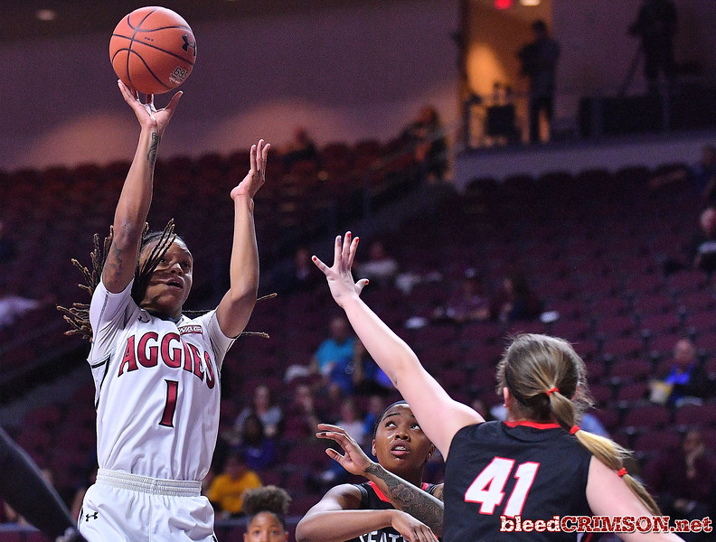 LAS VEGAS, NV - MARCH 09:  Jasmine Cooper #1 of the New Mexico State Aggies shoots against Kallin Spiller #41 of the Seattle Redhawks during a semifinal game of the Western Athletic Conference basketball tournament at the Orleans Arena in Las Vegas, Nevada. Seattle won 84-61.