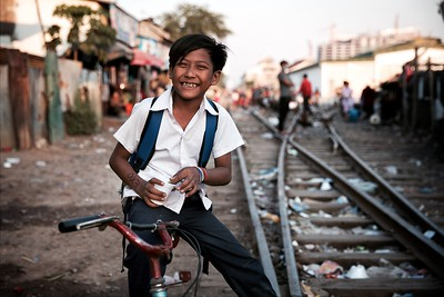 """Kasy, 11, Phnom Penh Railway Slums.   """"It takes me 30 minutes to ride to English lessons""""  Kasy had just finished class and was enjoying something he loves - ice-cream! When I asked him if he felt the same way about English, he said he likes it but he's not very good at it. In spite of this, he makes the hour-long journey each day to receive extra lessons in an effort to improve.  2016."""