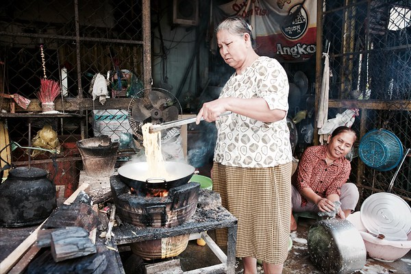 A local woman cooks lunch outside her home - White Building, Phnom Penh.  2016.