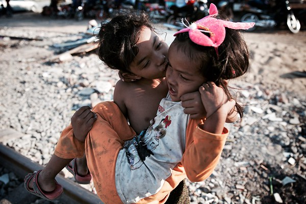Girls play outside their homes in the railway slums of Phnom Penh.  2016.