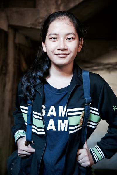 "Davry, 18, Phnom Penh.<br /> <br /> ""I love teaching kids. I want to listen to them, help them and motivate them!""<br /> <br /> Davry has a remarkable outlook on life for an 18 year old and growing up in a slum area in Phnom Penh has lead to her ultimate goal of helping the poor. Although she's had her fair share of challenges, what shines through is Davry's underlying determination. <br /> <br /> ""I would look at other kids and wonder why they had a mother and I didn't""<br /> <br /> Davry grew up in a small farming village in northern Cambodia. Her parents separated when she was 4 years old, effectively abandoning her, but thankfully a great-aunt in Phnom Penh took her in. These years were very tough for Davry:<br /> <br /> ""I had no one to turn to, as my aunty was busy working. I didn't know where my mother was and my father moved to Thailand for work. On top of this, I had to sell food in order to earn the 25 cents I needed to pay for school.""<br /> <br /> ""My NGO has made me stronger""<br /> <br /> Davry's life changed when she started going to classes at a local NGO. Here she began to feel more empowered through lessons in leadership, teamwork, debating and English to name a few. This then inspired Davry, along with a few others, to start their own organisation called 'Smile Group'. Their aim was to help the local community by providing school materials for children, as well as educating them in hygiene, waste management, recycling and other various social issues.<br /> <br /> ""I want to become a doctor and provide free healthcare for the poor""<br /> <br /> Davry's long term plans have meant she now places a lot of importance on her own education. She hit a hurdle at the end of last year however, as she didn't acquire the grades needed to get into university. This has meant repeating her final year of high school and for now, putting the Smile Group on hold. During my last conversation with Davry, she mentioned that one of her teachers had refused to let her sit an exam due to low attendance for a Saturday class, even though she explained that she has to work on weekends to pay for school. Her teacher was unrelenting however and Davry refuses to pay a bribe which is common practice in Cambodia.<br /> <br /> ""I don't want to find my mother until I'm successful. I want to show her that I don't need her"" <br /> <br /> At 18, Davry continues to live under her aunt's roof along with 4 of her cousins. Although Davry's father still works in Thailand, she caught up with him a year ago and met his new wife and son. She wishes she could receive his help and understanding, but believes it's not possible to share these feelings with him. As for her Mother, she thinks she's probably got another family somewhere … <br /> <br /> 2016."