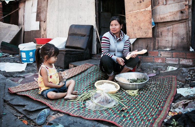 "Srey Neng, Sambok Chab Slums, Phnom Penh.<br /> <br /> ""I moved here from Takéo Province after my house burnt down.""<br /> <br /> Srey Neng described the living conditions in Sambok Chab as she prepared Khmer noodles with her 6 year-old daughter:<br /> <br /> ""There's no running water. We have to buy it in 50 litre drums that cost 10 cents. The rubbish you see on the ground is from the people who live here - no one comes to collect it.""<br /> <br /> 2016."