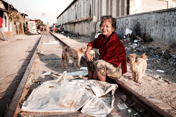 """Pov, 67, Railway Slums - Phnom Penh.   """"I've lived here since 1979""""  Pov dries cooked-rice on the railway tracks outside her home, which she then sells for 20 cents a kilo. She lives with her family, but said her husband passed away 5 years ago. She is still coming to grips with his loss as she was moved to tears when mentioning him."""
