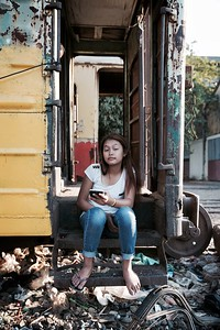Playing on her smart-phone - Railway Slums, Phnom Penh.  2016.