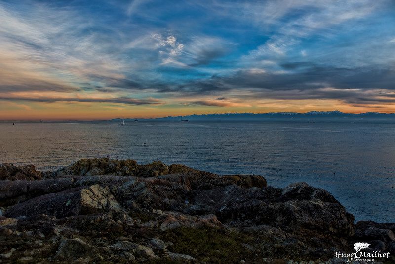 Sailboat passing by Victoria with the olympic mountains in the background at Sunset