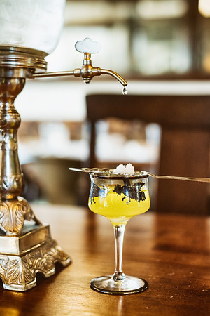Roux, French bistro and wine bar, 688 Park Avenue, Rochester, NY 14607. In this photo, ice water drips from a fountain onto a sugar cube and slotted spoon to distill absinthe.Photo by Brandon Vick Photography LLC, http://brandonvickphotography.com/