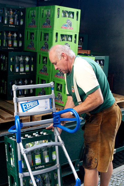Beer delivery man wears lederhosen, popular in Bavaria.