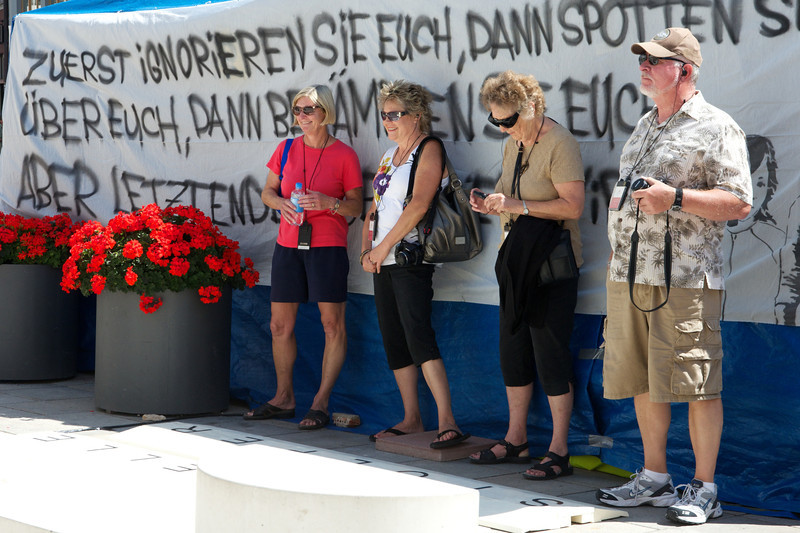 Tourists rest in the shade in front of a protest banner.