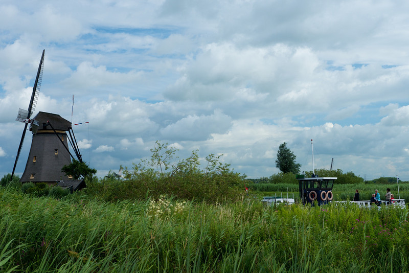 A small ship meanders up a canal.