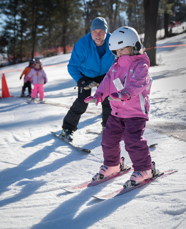 . Violet, 6, from Stow, gets a ski lesson on balance and turning from Nashoba Valley Ski Area instructor, Sean Grady, of Carlisle.   Photo: Scot Langdon / SUN
