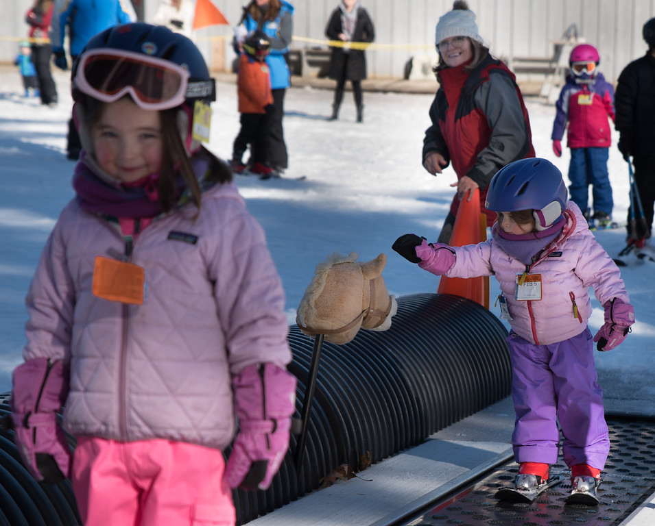 . Eloise Jacobellis, 2 1/2 , from Carlisle (R) touches the stuffed horse head signifying the moment she can get on the ski lift at Nashoba Valley, to give space between her and her sister, Lia, 4 1/2, (L) while their grand mother, Silvia Ross of Chelmsford, looks on.   Photo: Scot Langdon / SUN