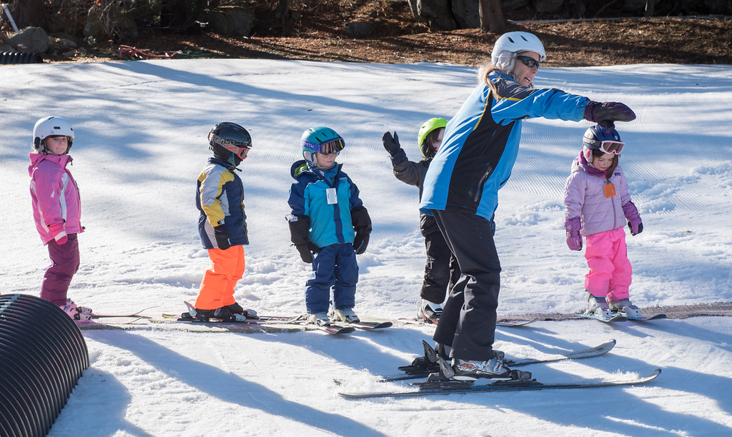 . Nashoba Valley Ski Area instructor, Mary-Anne Noddin-Poulin of Cape Cod, guides a small group of area kids in some of their first ski lessons Monday afternoon.  Photo:  Scot Langdon / SUN