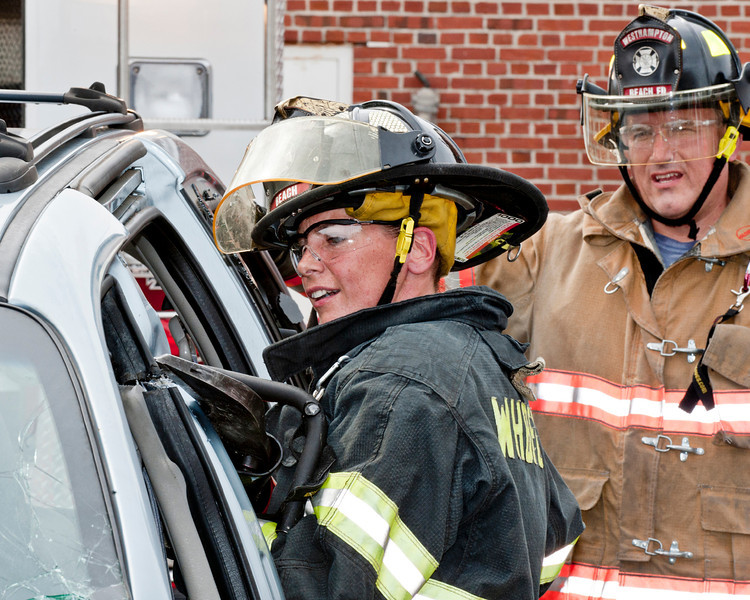 "Firefighter Gypsy Adams demonstrates the cutters, known to many as the ""jaws of life"" as volunteer John Cable looks on."