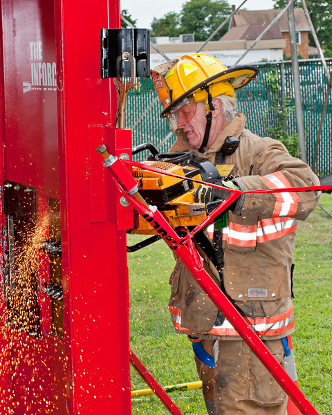 Sparks fly as Westhampton Beach Fire Department's Lieutenant Paul Hoyle saws his way through a door.