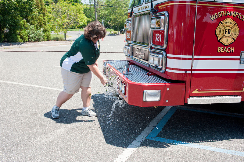 Caption: The Westhampton Beach Fire Department officially entered its new pumper 7-8-1 into service at a traditional wet down ceremony held at the department's Sunset Avenue firehouse on Sunday. Department Captain Tonya Schunk gave the new truck a champagne christening in front of approximately one hundred firemen and guests. The new vehicle, which was delivered to the department in March, was built by the Seagrave Company of Clintonville, Wisconsin. It is equipped with a 1500 gallon per minute pump and a 750 gallon tank as well as 3000 feet of fire hose of various diameters. It has an 8 KW generator and an on board foam tank. Its body is made of stainless steel which is important in a seaside community. The truck, which can carry up to eight firemen, has made about thirty calls since the factory delivered it in March. It replaces a truck which the department has owned since 1992.