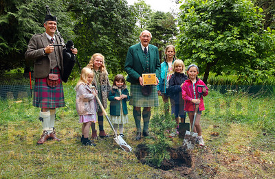Lord Godfrey Macdonald accompanied by some local children who helped him plant a Vietnamese Cypress tree and piper Decker Forrest.
