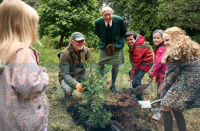 Local children and tree specialist Andrew Peters,  were on hand to help Lord Godfrey Macdonald plant a Vietnamese Cypress tree, in the gardens of Armadale Castle.