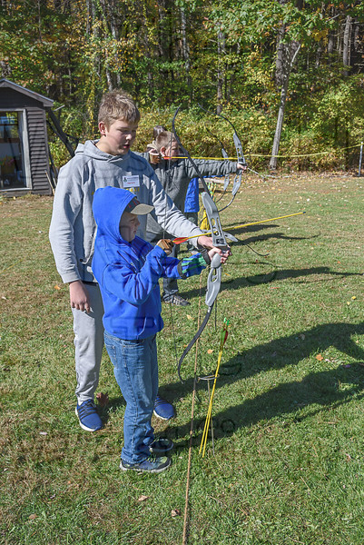 Volunteer instructor Gage Laurie shows Mason Stratton how to hold a bow at Saturday's WHOA event in Russell.