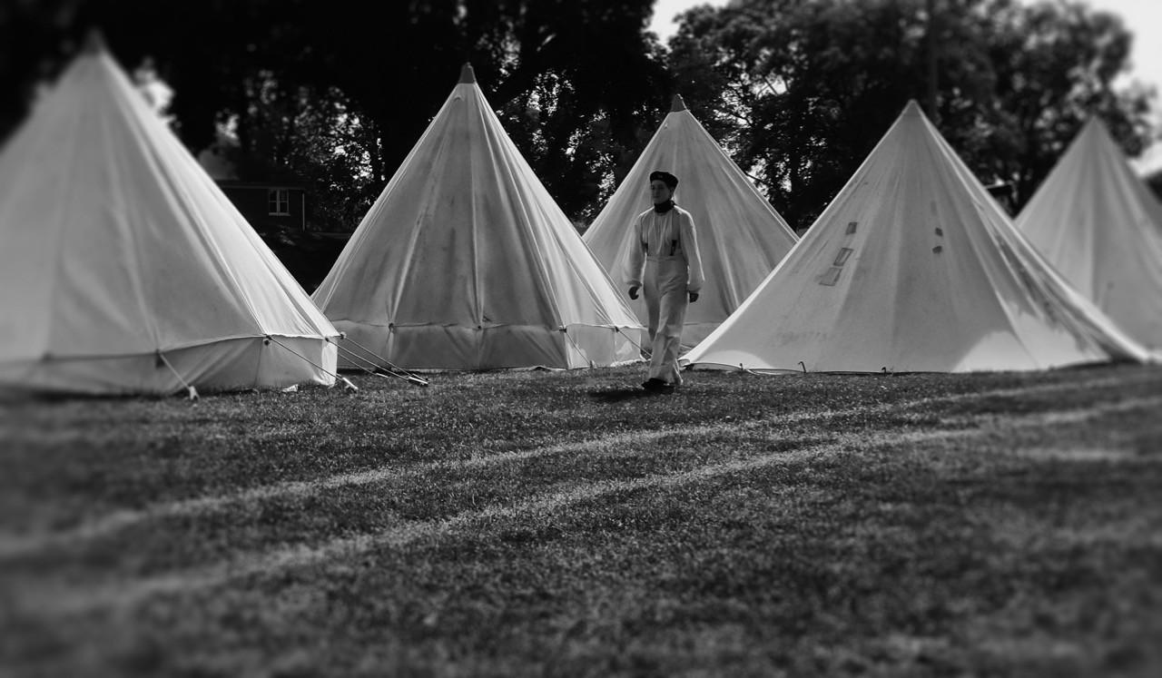 Baker walkiing among tents at Fort Malden