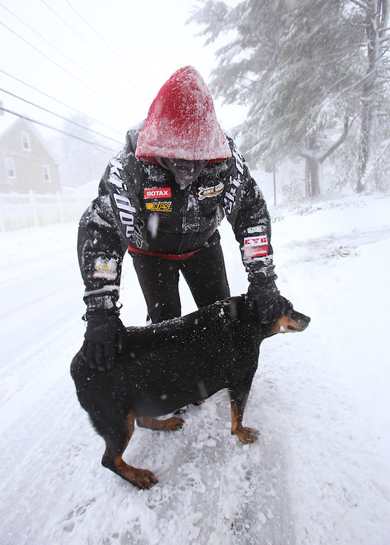. David Duarte of Tewksbury on East Street with his brother-in-law\'s dog, Raja, 14, who enjoys the snow. (SUN/Julia Malakie)
