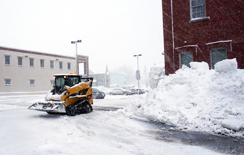 . A snow removal machine cleaning the parking lot at Lowell Senior Center. (Chris Tierney / The Sun)