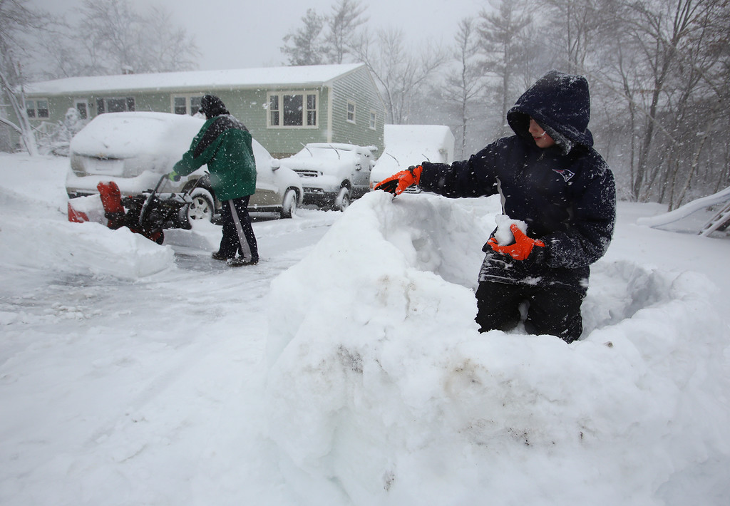 . Sean Morgan, 11, of Tewksbury, builds a snow fort while his father Chris Morgan clears their driveway on Jerome Road. (SUN/Julia Malakie)