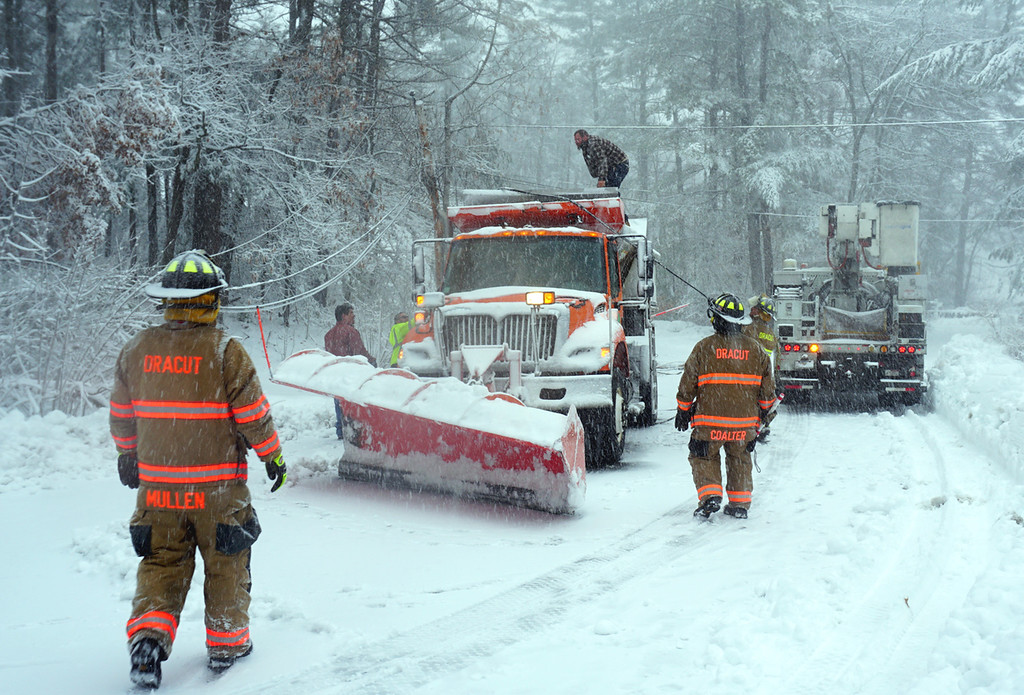 . Dracut Fire men Chris Coalter and Stephen Mullen at the scene of Dracut DPW plow driven Jason Antifonario (top of truck) which hit low hanging wires and knocked down two poles on Kevin Road in Dracut. National Grid was dispatched out of Methuen and shut off the power before the wires could be removed. Nobody was hurt and Antifonario continued plowing. (The Sun / Chris Tierney)
