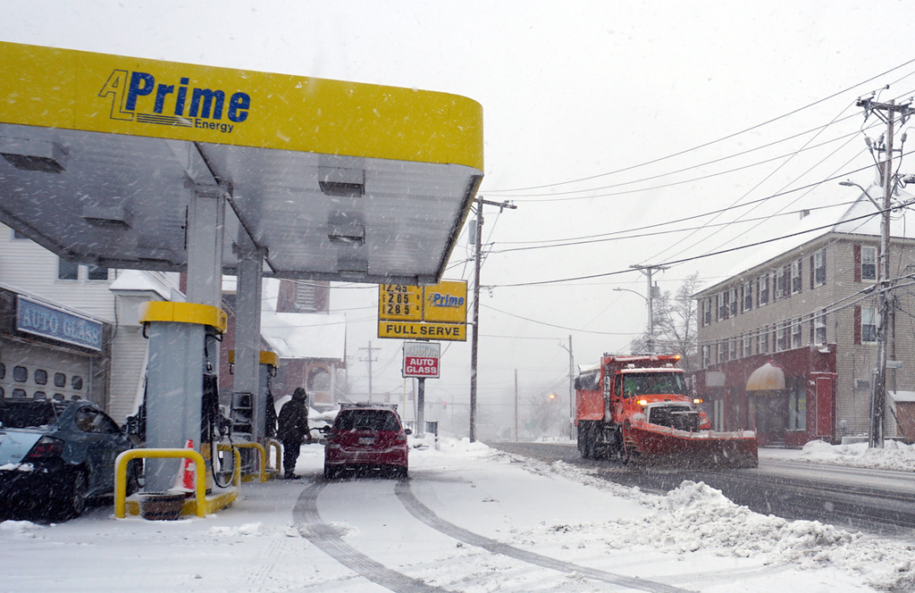 . Cars filling up at Prime gas station on Mammoth Road in Lowell, as City plow goes by keeping strets  clean. (The Sun / Chris Tierney)