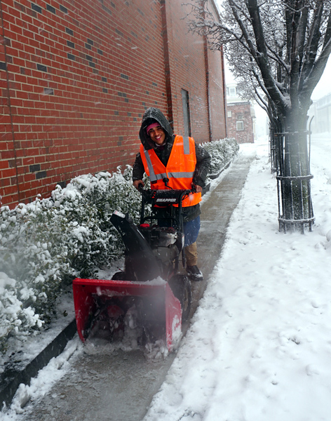 . Jean Santos of Lowell, an employee of Market Basket of Wood Street cleans off the sidewalk on Broadway Street (The Sun / Chris Tierney)