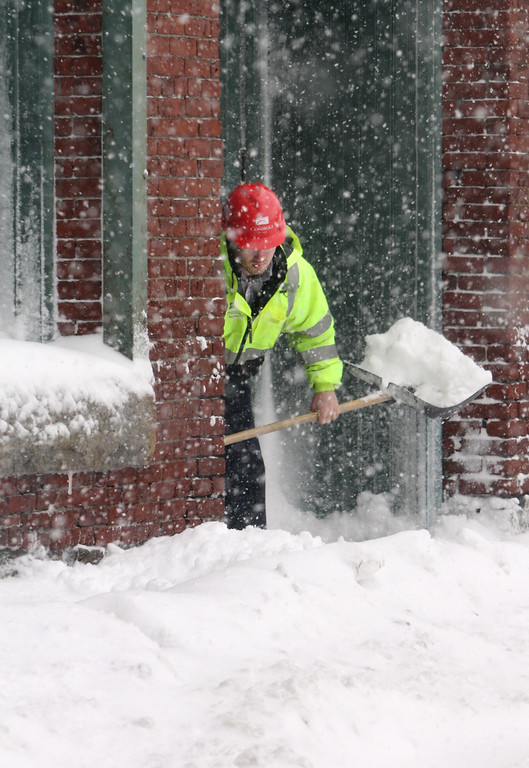 . Bryan Gaiss of Boston shovels a sidewalk on Green Street in downtown Lowell. (SUN/Julia Malakie)