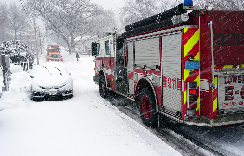 . Lowell fire arrives at Crawford Street  to remove low hangingwires so City Plow Truck can pass. (The Sun / Chris Tierney)