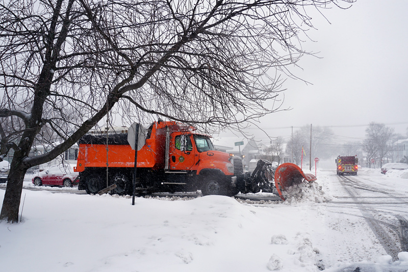 . Lowell fire in background leaves Crawford Street after removing low hanging cable wires so city plow can get by. (The Sun / Chris Tierney)