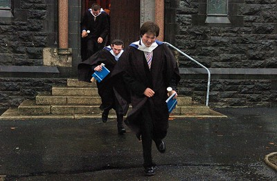 Provision 251006 Paul Falvey (Kilkenny), Johnathan Ennis (Waterford) and Joseph Doyle (Carlow) run for cover after their graduation ceremony in a WIT.  They all graduated with a BA in Legal Studies. PIC Bernie Keating/Provision