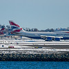 A BA 747 taxis to the runway at Logan Airport while a Virgin America flight takes off.