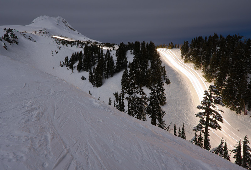 This was my first attempt at a long exposure of the team grooming some of our slopes at night. The slope illumination came from the almost full moon veiled behind a thin layer of cloud.  There was no wind. The exposure time was just shy of 14 minutes.<br /> <br /> I'll continue to try to improve this type of shot - first item to work on will need to be to find a way to tone down the glare from the cat's lights (I had to hit the light trail pretty hard in Photoshop to bring out the streaks even as much as I did). Second will be finding runs where the cats can stay in line without needing to break formation to do a crossover or pick up a berm or whatnot (the last cat in this shot had to jump into the center to clean something up and thus muddied the streak lines). Third will be finding a run where I can set up my tripod and get the run and some sort of foreground/background element into the shot.  And lastly, but certainly not least is finding a night where my positioning, our workload and the weather all comes together to make the above happen.  Yikes, that's a lot of stuff to pull together...<br /> <br /> Location: Outer and Inner Limits, Mt. Hood Meadows ski area, Oregon<br /> <br /> Lens used: 10-22mm f3.5-4.5