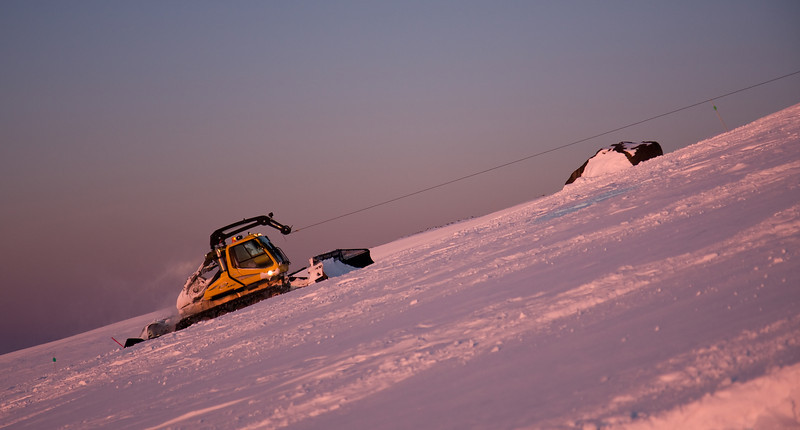 Here, Mike Rowley winch-packs and -grooms the intermediate run of Boulevard above the tree-line in the morning alpenglow.  The 'big rock' seen in this shot is a prominent landmark on the upper mountain at Meadows.<br /> <br /> Lens used: 17-55mm f2.8 IS