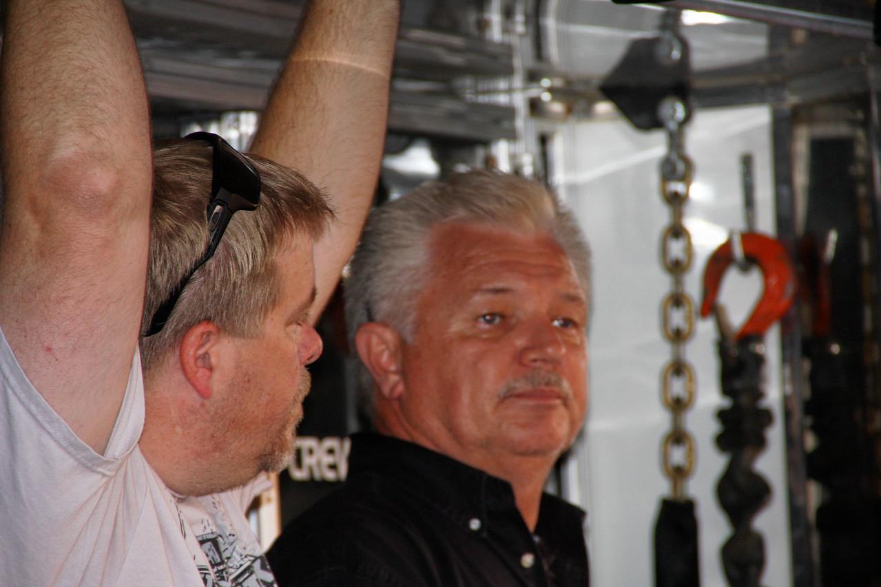 Kelley Carlton hangs by his thumbs as FASTRAK owner Stan Lester looks on.