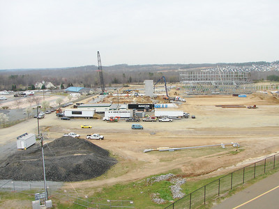 The view from the top of the dirt track stands, looking west. The construction trucks are parked in the dirt track pit area. Just past the old pit area will be the begining of the drag strip. Running past the stands, which face this way.