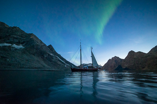 Sailboat Arktika anchored in Kangertigtivatsiaq fjord, east Greenland. The season's first northern lights on the sky.