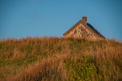 Warm early morning sunlight washes over an old house on Cheticamp Island  near the Acadian fishing town of Cheticamp on the western side of Cape Breton Island.