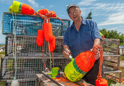 A  fisherman paints marker bouys beside a pile of lobster traps in the Shelburne County fishing community of Jordan Bay