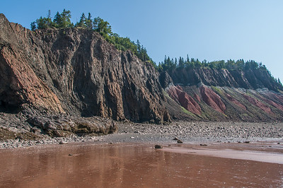 These colourful cliffs at Five Islands Provincial Park are typical of those found all along shores of the Bay of Fundy in Nova Scotia. The world's highest tides occur twice daily in the Bay and at low tide visitors can walk the ocean floor in search of fossils and other marine treasures.