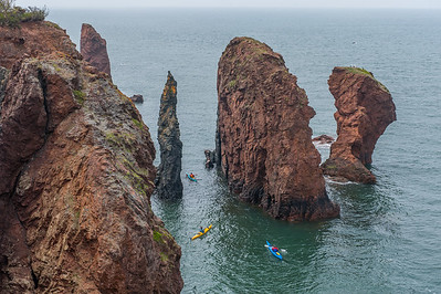 Kayakers explore  the 'Three Sisters' rock formations that rise from the waters of the Bay of Fundy at Eatonville in Cape Chignecto Provincial Park. At low tide, it is possible to walk on the sea bottom around these rocks.