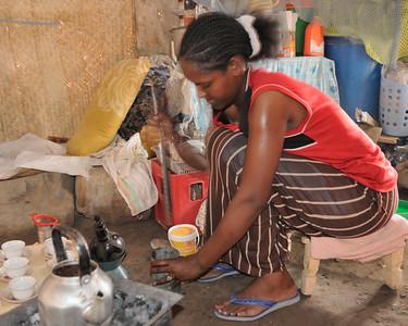 Femme qui concasse des grains de café torréfié