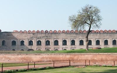 Intérieur du Fort Rouge d'Agra construit par Akbar. C'est un palais résidentiel pour son fils Jahângîr. À partir de ce moment-là, le fort n'est plus seulement une place militaire mais aussi un lieu de résidence. La construction du Fort, en grès rouge, commença en 1565, et s'acheva en 1571, sous le règne de Shah Jahan, petit-fils d'Akbar. Il marque la naissance du style impérial moghol, fusion de l'art perse du XVème siècle et de la tradition architecturale hindo-musulmane prémoghole. Le Fort d'Agra est impressionnant : non seulement il mesure 2.4 km de circonférence, mais en plus c'est une forteresse entourée d'une double enceinte. Un fossé large de 9 m et profond de 11m sépare le mur extérieur, haut de 12 m, de l'enceinte intérieure, haute de 21 m. A l'intérieur de ces murailles ont été édifiés plusieurs palais et mosquées, de grès rouge et marbre blanc. C'est un véritable labyrinthe de bâtiments qui forme une petite ville dans la ville. Ces monuments abritaient en leur temps des chambres, des halls de réception privés et publics, des appartements d'été et d'hiver ainsi que des lieux de prière.