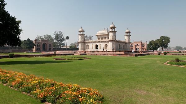 """Mausolée d'Itmad-ud-Daulah, parfois appelé """"petit Taj"""" : c'est le tombeau de Mîrzâ Ghiyâs Beg, beau-père de l'empereur Jahângîr. Tandis que l'empereur Jahangir se consacrait aux plaisirs de la poésie ou du vin, son épouse, d'une très grande beauté, Nur Jahan dirigeait l'Etat avec son père, le Persan Mirza Ghiyas Beg, honoré du titre d'Itmad-ud-Daulah (""""pilier de l'Etat""""= Vizir). On l'appela ensuite Noor Jehan, lumière du monde et sa nièce fut Mumtaz Mahal, la dame du Taj Mahal. A la mort de celui-ci, elle lui édifia un tombeau qui est une merveille de délicatesse. Sa construction débuta en 1622 pour s'achever en 1628. Son architecture rappelle celle du Taj Mahal Ce fut le premier monument en Inde construit en marbre de ce type à présenter un travail d'incrustation de mosaïques de style perse ou """"Pietra Dura"""". Le mausolée est plus petit et plus ramassé que le Taj Mahal, mais sa séduction tient justement à cette échelle plus humaine et ses ornements sont superbes."""