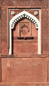 Détail d'un mur de cour intérieure dans le Fort Rouge d'Agra construit par Akbar. C'est un palais résidentiel pour son fils Jahângîr. À partir de ce moment-là, le fort n'est plus seulement une place militaire mais aussi un lieu de résidence. La construction du Fort, en grès rouge, commença en 1565, et s'acheva en 1571, sous le règne de Shah Jahan, petit-fils d'Akbar. Il marque la naissance du style impérial moghol, fusion de l'art perse du XVème siècle et de la tradition architecturale hindo-musulmane prémoghole. Le Fort d'Agra est impressionnant. A l'intérieur de ses murailles ont été édifiés plusieurs palais et mosquées, de grès rouge et marbre blanc. C'est un véritable labyrinthe de bâtiments qui forme une petite ville dans la ville. Ces monuments abritaient en leur temps des chambres, des halls de réception privés et publics, des appartements d'été et d'hiver ainsi que des lieux de prière.